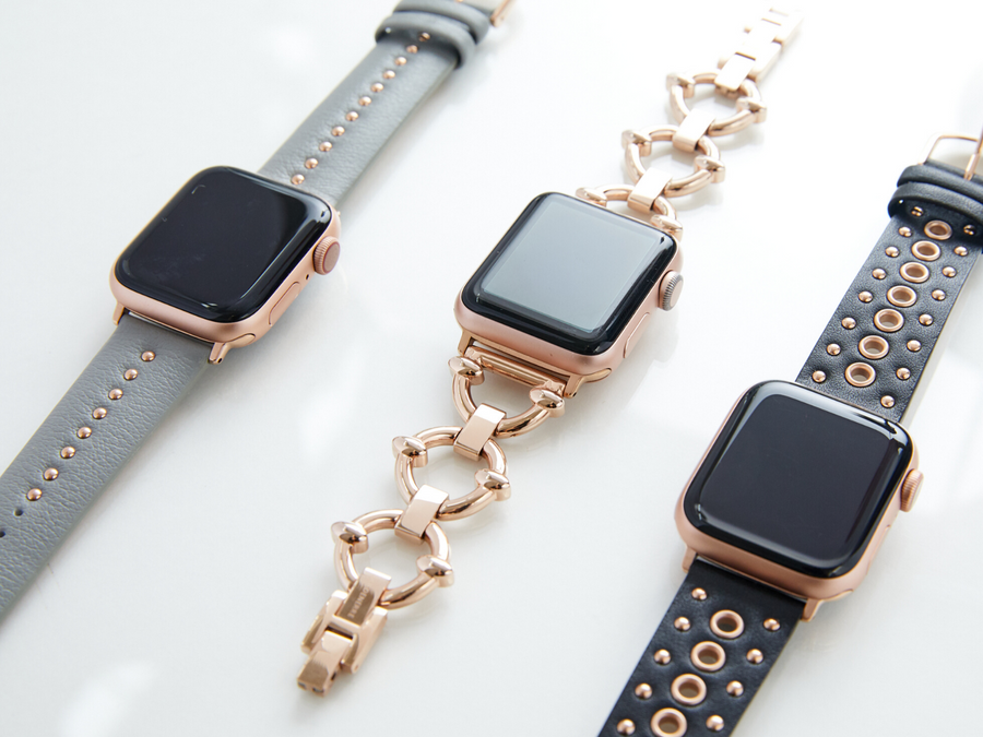 Trio of rose gold Apple Watch bands, shown from left to right with silver mini stud band, rose gold classic link bracelet for the Apple Watch, and grommet stud band for the Apple Watch, all by Goldenerre