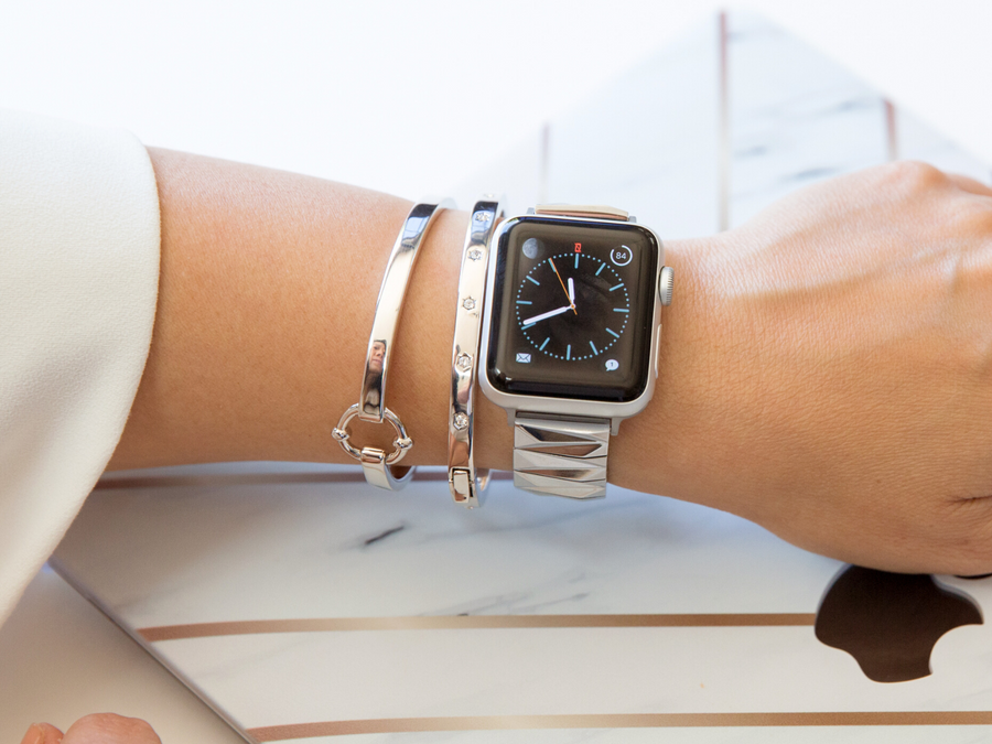 Silver women's bracelet for the Apple Watch, made of shiny pyramid links that wrap around the wrist. Shown here with a silver apple watch , silver rhinestone bracelet, and silver classic link band against a laptop background