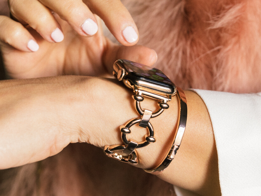 Stunning rose gold women's apple watch bracelet, shown with a woman interacting with the Apple Watch screen.