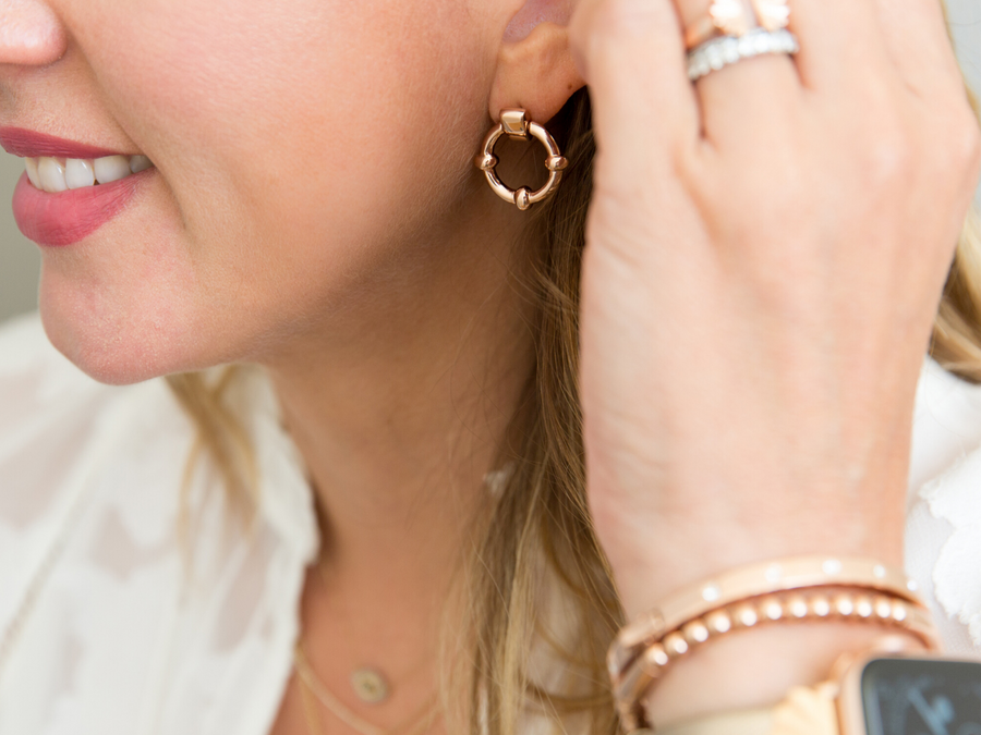 woman holding her hair back to show her classic link earring - a rose gold circle with embellishments at every quarter of the circle to add detail and shine
