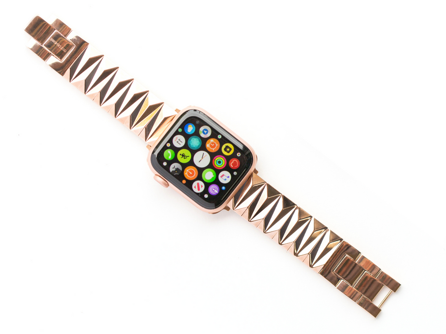 Cool rose gold women's bracelet for the Apple Watch, made of shiny, rose gold pyramid links. Shown on a Gold aluminum Apple Watch with screen lit up. On a white background.