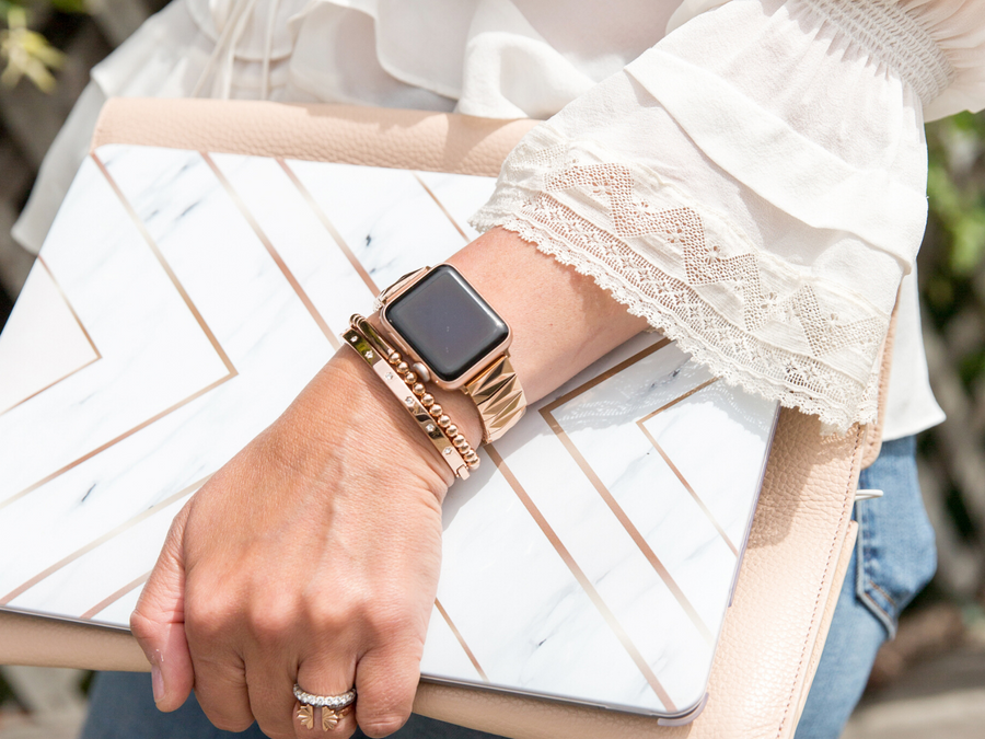 Women carrying laptop and pink laptop club, wearing a Goldenerre rose gold pyramid bracelet for the Apple Watch, rose gold beaded bracelet, and rose gold rhinestone bracelet