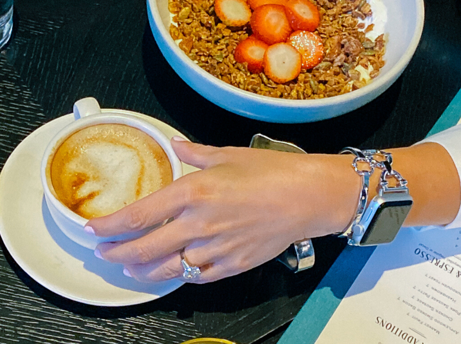 Woman wearing silver classic link bracelet for the Apple Watch, at breakfast with a cup of coffee