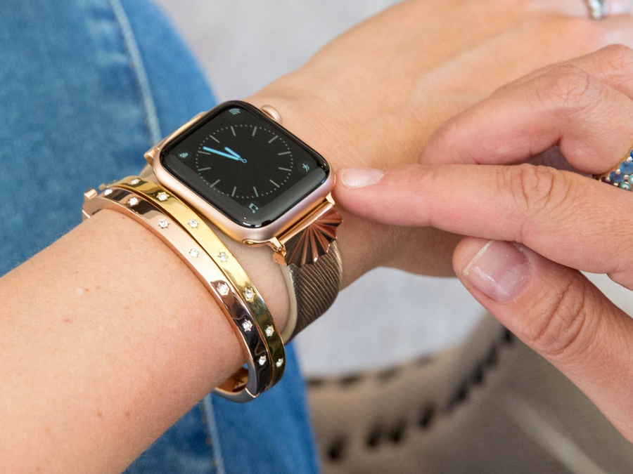 Goldenerre Rose Gold starburst band on a gold saffiano band with a rose gold Apple Watch. Shown stacked with a rose gold and yellow gold rhinestone bracelet. Woman is wearing a denim jumpsuit and getting ready to tap the Apple Watch with her finger.
