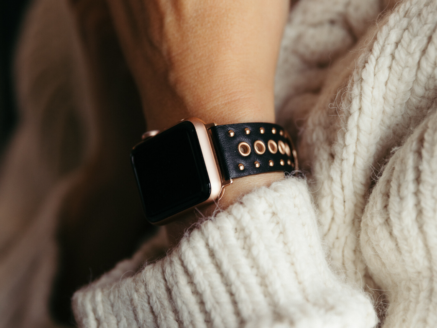 Woman wearing Apple Watch with luxe Goldenerre black leather watch band embellished with shiny, rose gold grommets.