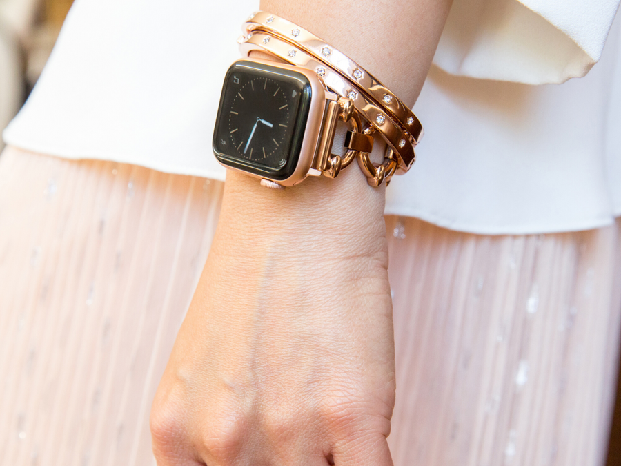 Woman with wrist by side, showing rose gold apple watch with Goldenerre rose gold classic link bracelet and two rose gold rhinestone bangles