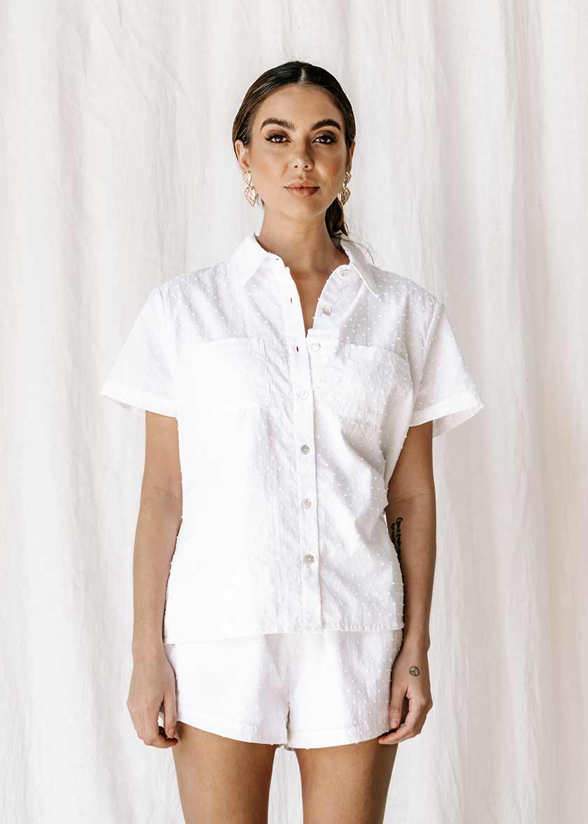 The new everyday blouse that will take you from sunrise to sunset.  The new everyday blouse that will take you from sunrise to sunset, the Capri Shirt is so comfortable you'll never want to take it off. Button up white textured blouse / shirt, short sleeve super soft. Shell button detail 100% high-quality cotton Beautiful textured dot fabric Pockets Split detail on sides Oversized fit Made from the highest quality cotton fabric, that is cool & breathable to wear  ETHICALLY MADE IN INDONESIA