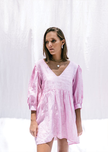 pink linen smock dress on young women flowy fabric puffy sleeves with deep v neckline front shot