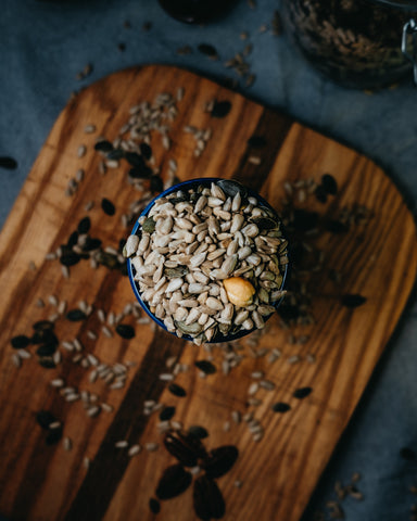 pumpkin seeds sitting in a bowl on top of a wooden cutting board