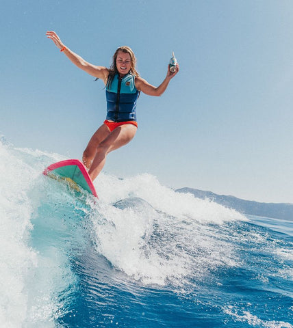 female surfer holding a wave soda while surfing a wave