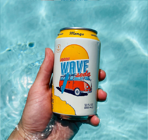 hand holding mango wave soda in the water of a pool