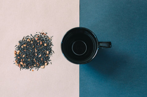 black tea in a mug with a dark blue background and a light pink background
