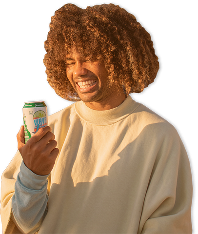 man smiling at his new wave soda cucumber flavor