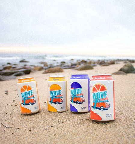 four different varieties of wave soda sitting in the sand