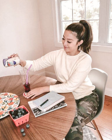 woman sitting at a table pouring a blackberry wave soda