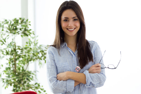 A smiling woman wearing Oxy-Angel air ionizer while holding eyeglass