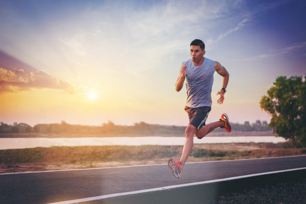 Athlete running beside lake to energize with negative ion