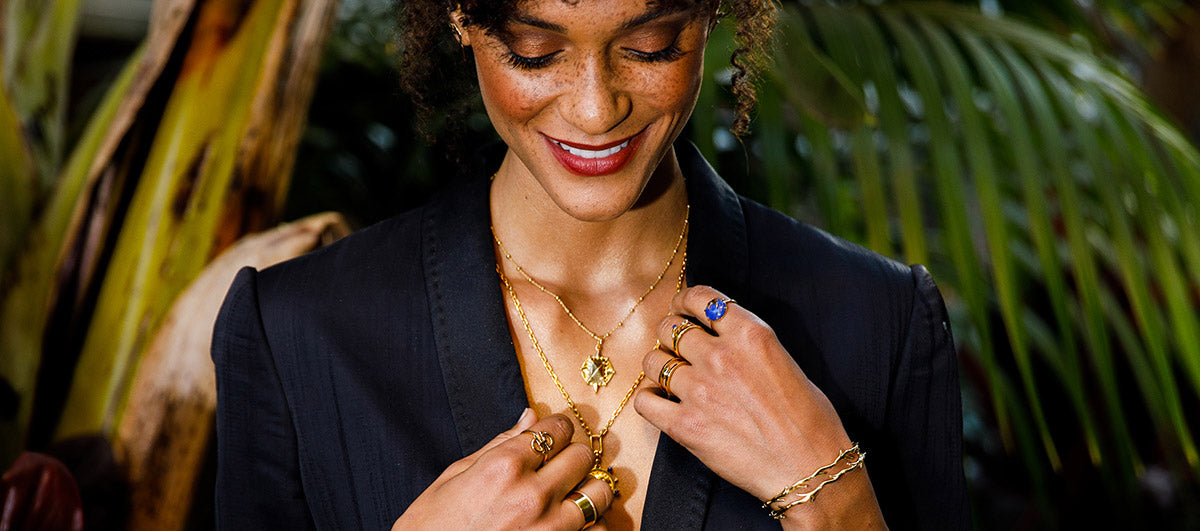 Model in jungle wearing midnight botanica jewelry looking down with a smile