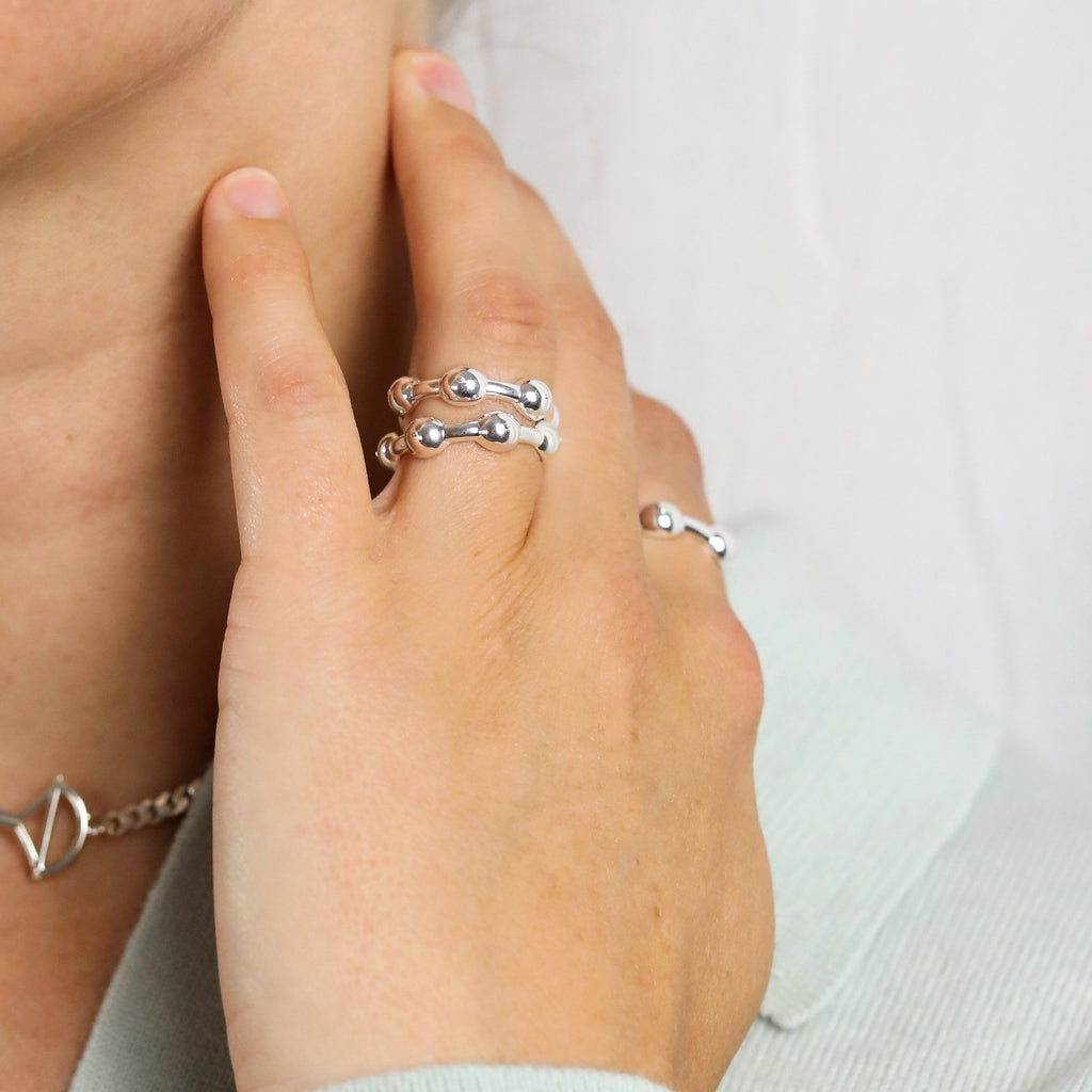 Two stacked silver seeded eternity rings on model