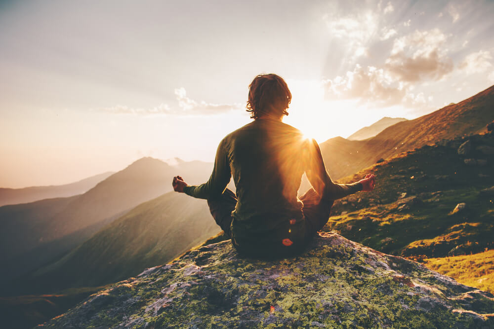 Man sitting on a mountain peak, he's in a meditation positions with the sun cast over him