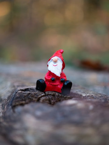 small-santa-ornament-sitting-on-a-tree-log-in-the-forest