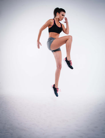 Fit woman wearing athletic gear jumping with a white background