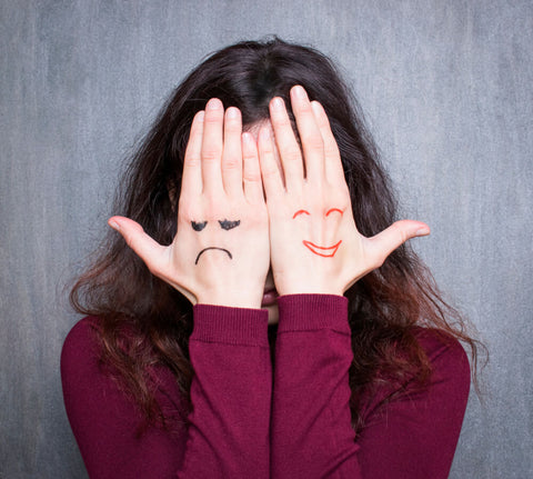 A photo of a girl holding her hands up. One hand has a picture of a smiling face, the other has a sad face.