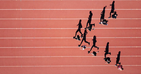A birds eye view of an athletic track, the runners are in a V shape