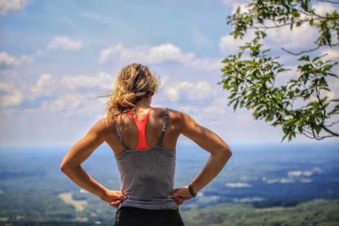 A photo of the back of a woman, she's standing on a cliff-top with her hands on her hips. She looks like she has just been working out.