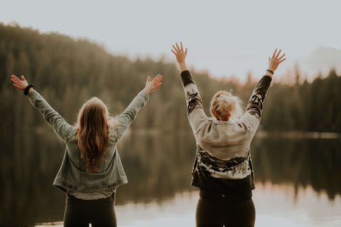 two women looking over a beautiful lake with their arms raised in joy!