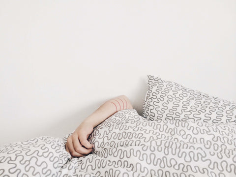 White sheets with an arm sticking out, suggesting that the person is fast asleep