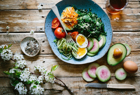 A birds eye view of a bowl, filled with healthy, nourishing foods, like eggs, leafy greens and advocado