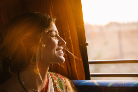 a women sitting next to a window with the sun shining on her face, getting that sweet dose of vitamin d