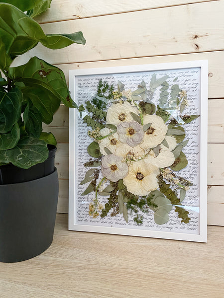Our white wood frame showcases this pressed wedding bouquet with a handwritten background.