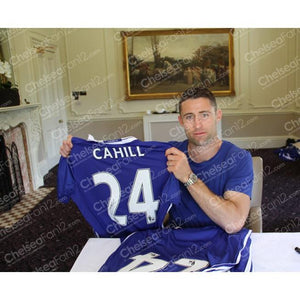 Gary Cahill holding up a chelsea shirt after signing it