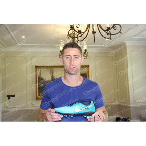 Gary Cahill signed football boot, Cahill holding up his signed boot