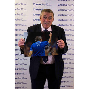 Bobby Tambling holding up his signed 'Welcome Home' photograph
