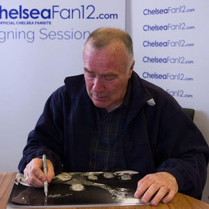 Ron Harris hand signing a photo of him holding up the FA Cup in 1970
