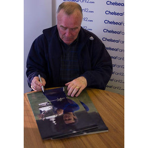 Close up of Ron Harris hand signing a photo of him holding the FA Cup