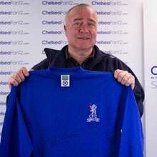 Load image into Gallery viewer, Ron Chopper Harris holding up a 1970 Wembley Retro Shirt, after signing it during a private session with ChelseaFan12