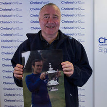 Load image into Gallery viewer, Ron Harris holding up a photo of him with the FA Cup, after signing the photo in a signing session with ChelseaFan12