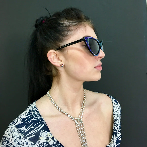 Model Julian Stavole rocking Femme Fatale sunglasses encrusted in shimmering colorshifting paradise crystals — Made with Swarovski