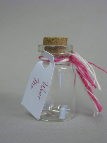"""Wear Me"" A pair of triangle acrylic pale pink stud earrings in a glass bottle with cork stopper"