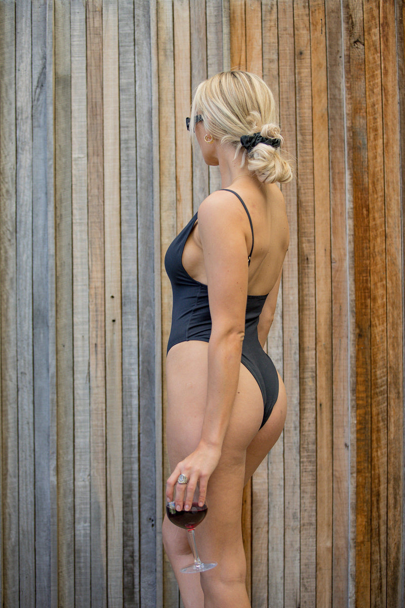 Black one piece swimsuit with luxe gold details in sustainable and eco-friendly fabric - Amni Soul Eco, features an 80's style high leg and flattering scoop neck line