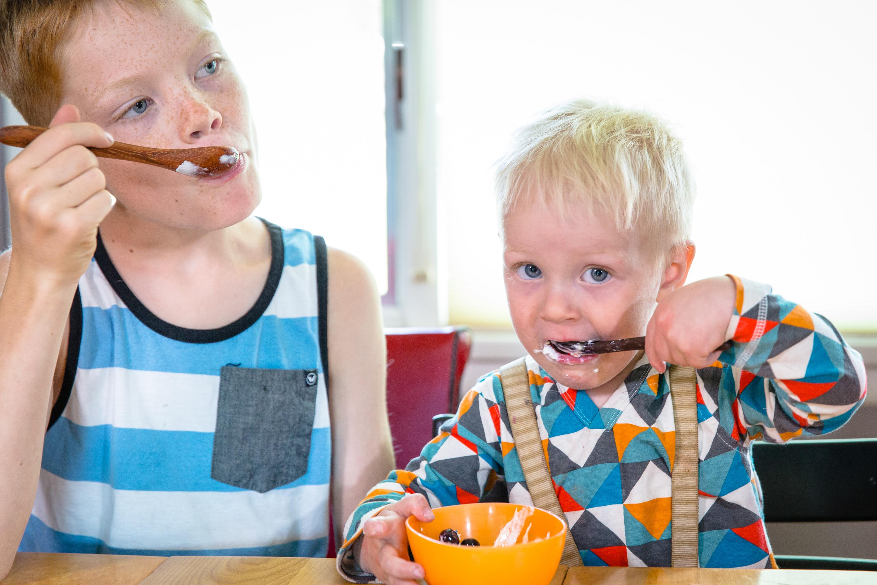 Kids using wooden spoons for eating