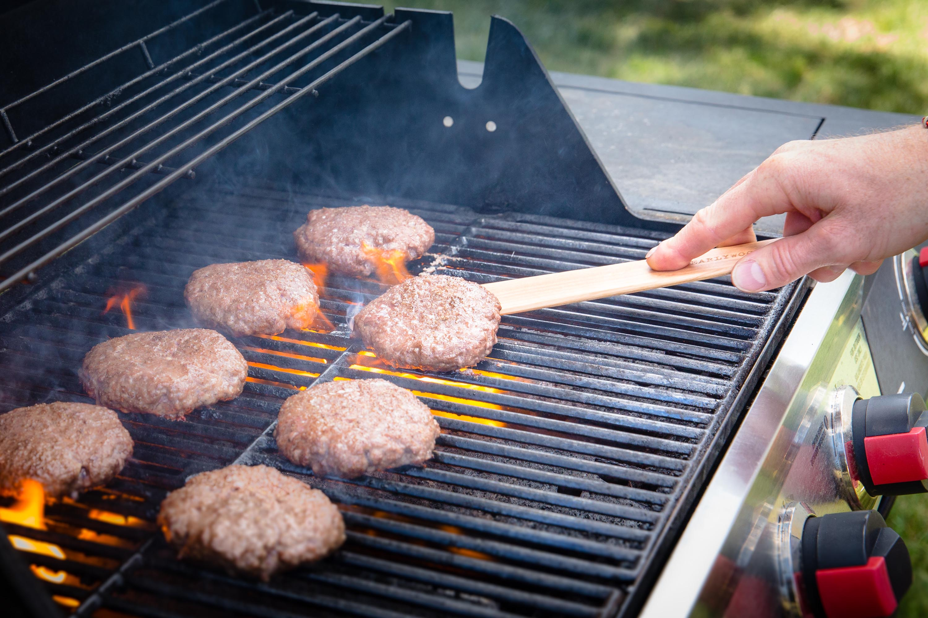 Grilling burger meat using wooden spatula