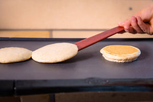 flipping pancakes with thin wooden spatula - Earlywood