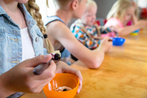 line of kids using customized wooden spoons for eating yogurt - Earlywood