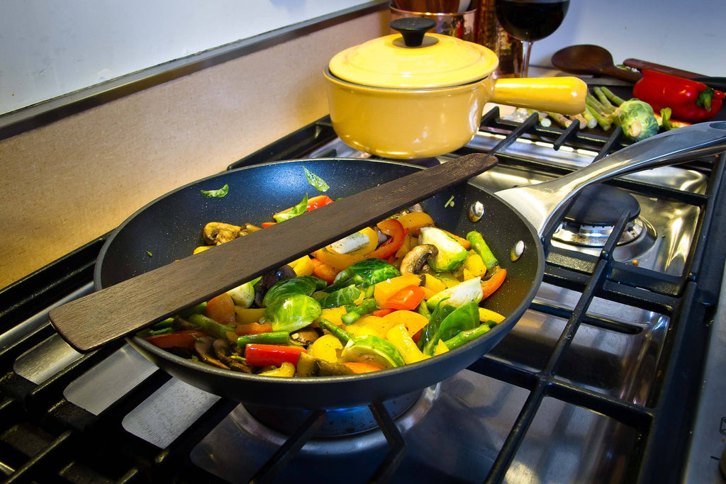 Large wood spatula sitting on pan cooking vegetables - Earlywood