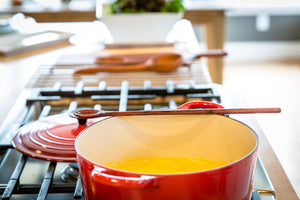 wood tasting spoon sitting on le creuset dutch oven with soup - Earlywood